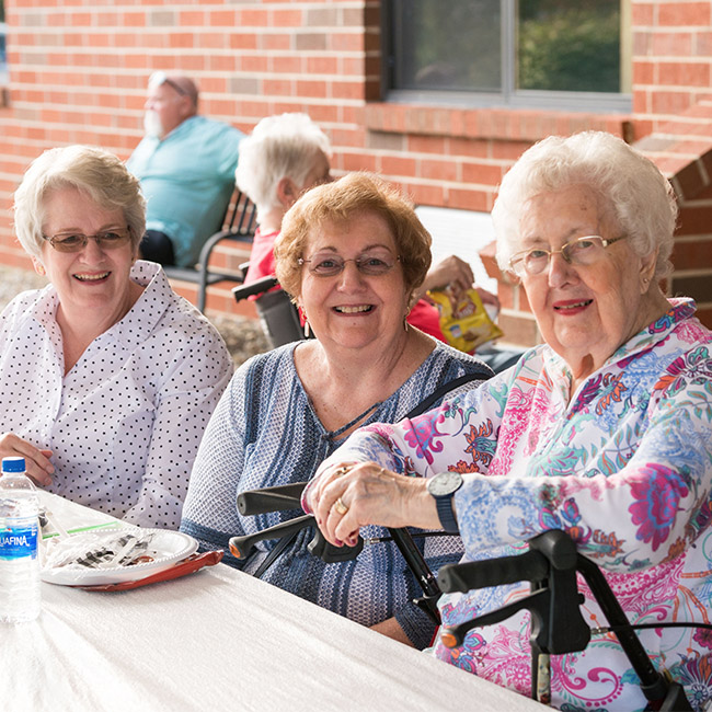 seniors smiling and talking outside of assisted living center