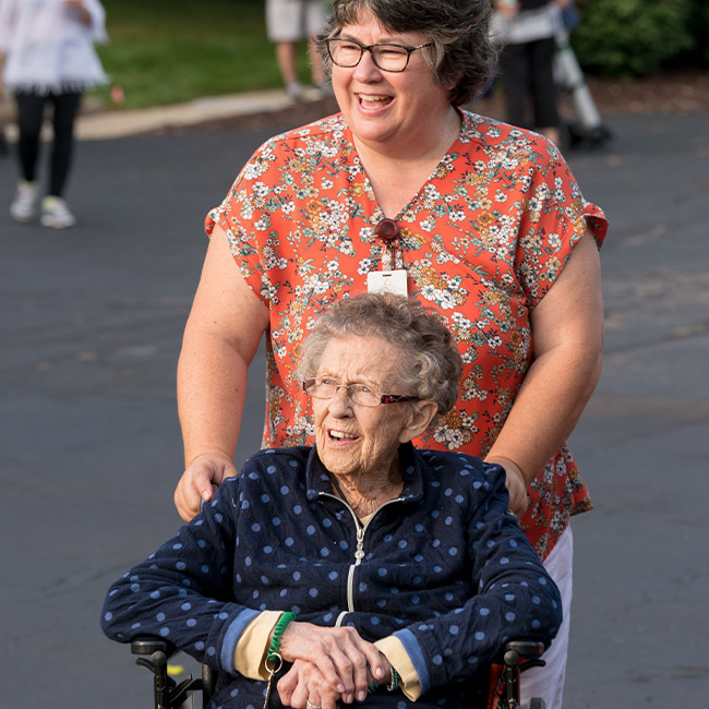 staff proving specialized senior care to elderly woman in wheelchair