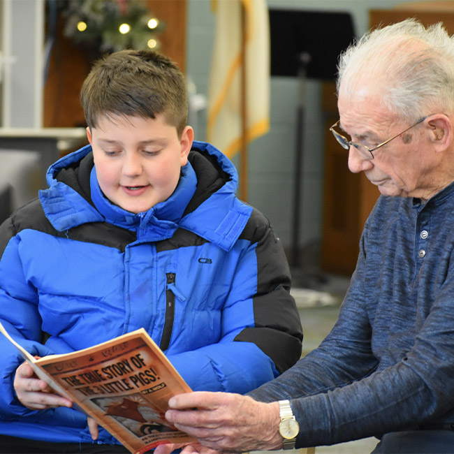 grandson reading book with grandfather in Kalamazoo senior home