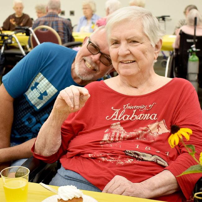 man visiting with elderly mother in senior care center